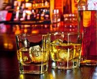 Gläser Whisky mit Eis auf Bartisch nahe Whiskyflasche auf warmer Atmosphäre Stockbild