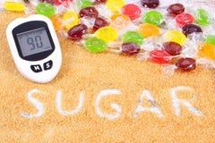Glucometer、五颜六色的糖果和被颗粒化的棕色蔗糖,糖尿病的概念 库存照片
