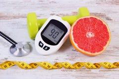 Glucometer、听诊器、新鲜的葡萄柚和哑铃健身的,糖尿病,健康生活方式 库存照片