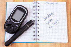 Glucometer与柳叶刀设备和擦亮剂题字世界在笔记本的糖尿病天 免版税库存图片