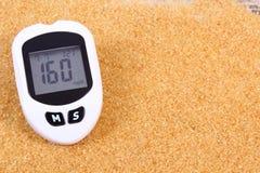 Glucometer和被颗粒化的棕色蔗糖,糖尿病的概念 库存图片
