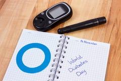 Glucometer, światowy cukrzyca dzień pisać w notatniku i błękitnym okręgu, symbol cukrzyk obraz stock