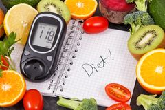 Glucometer με το αποτέλεσμα του επιπέδου ζάχαρης, φρούτα με τα λαχανικά και σημειωματάριο με τη διατροφή λέξης Υγιή τρόφιμα για τ στοκ εικόνες με δικαίωμα ελεύθερης χρήσης