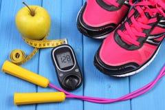 Glucometer, ботинки спорта, свежее яблоко и аксессуары для фитнеса на голубых досках Стоковое Фото