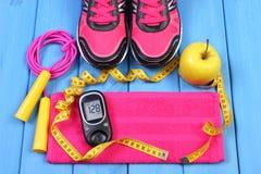 Glucometer, ботинки спорта, свежее яблоко и аксессуары для фитнеса на голубых досках, космоса экземпляра для текста Стоковая Фотография RF