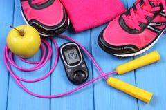 Glucometer, ботинки спорта, свежее яблоко и аксессуары для фитнеса на голубых досках Стоковая Фотография RF