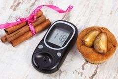 Glucometer, булочки с сливами и ручками циннамона на деревянной предпосылке, диабете и очень вкусном десерте стоковые изображения