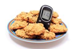 Glucometer и печенья овсяной каши на белой предпосылке Стоковое Фото