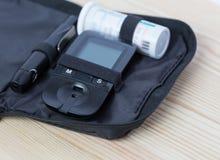 Glucometer и прокладка испытания лежат в случае сумки Стоковое Изображение