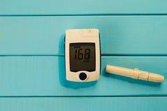 Glucometer на голубой предпосылке сахара в крови Концепция диабета стоковые фотографии rf