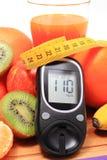 Glucometer, свежие фрукты с рулеткой и стеклом сока стоковая фотография rf