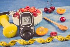 Glucometer с уровнем сахара результата, овсом шелушится с плодоовощами, гантелями и сантиметром, диабетом, уменьшением и здоровым Стоковое Фото
