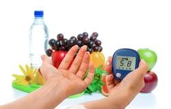 Glucometer для уровня глюкозы и здоровых натуральных продуктов на белой предпосылке Принципиальная схема мочеизнурения стоковые фото