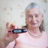 医学、年龄、糖尿病、医疗保健和人概念-有glucometer的资深妇女检查血糖水平的在 免版税库存照片