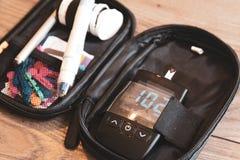 Glucometer apparat som visar resultat efter ett prov av glukosnivån arkivbild