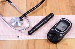 Glucometer avec le dispositif et le stéthoscope de bistouri sur le graphique d'électrocardiogramme Photos stock