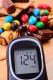 Glucometer avec le tas des bonbons sur la surface en bois, le diabète et la nourriture malsaine Images libres de droits