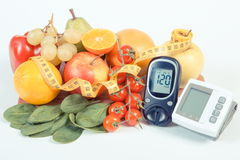 Glucometer, blodtryckbildskärm, frukter med grönsaker och cm, sund livsstil Arkivfoto