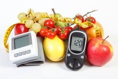 Glucometer, blodtryckbildskärm, frukter med grönsaker och cm, sund livsstil Royaltyfri Foto