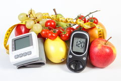 Glucometer, blood pressure monitor, fruits with vegetables and centimeter, healthy lifestyle Royalty Free Stock Photo