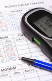 Glucometer and blue pen on medical forms for diabetes Royalty Free Stock Photos