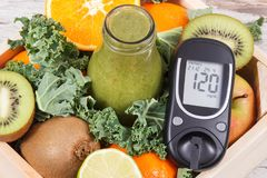 Glucometer for checking sugar level and coctail from fruits with vegetables as healthy dessert containing vitamins and minerals stock photography