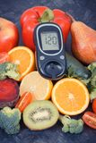 Glucometer for checking sugar level with fruits and vegetables containing vitamins, healthy eating for diabetic stock photography