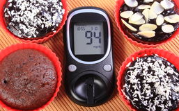 Glucometer and chocolate muffins in red cups Royalty Free Stock Photography