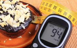 Glucometer, chocolate muffins and tape measure Stock Image
