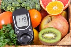 Glucometer con el nivel del azúcar y las frutas naturales con las verduras Diabetes y comida nutritiva que contienen los minerale imagenes de archivo