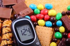 Glucometer con il mucchio dei dolci e dello zucchero bruno della canna, alimento non sano Fotografia Stock