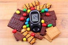 Glucometer con il mucchio dei dolci su superficie di legno, su diabete e su alimento non sano Immagine Stock