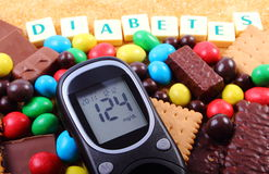 Glucometer, dolci e zucchero bruno della canna con il diabete di parola, alimento non sano Fotografia Stock Libera da Diritti