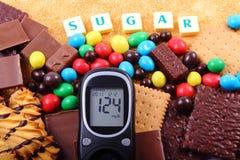 Glucometer, dolci e zucchero bruno di canna con lo zucchero di parola, alimento non sano Immagine Stock