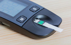 The glucometer is enlarged on the wooden table on the left side. Royalty Free Stock Image