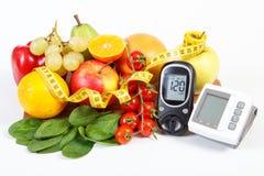 Glucometer för att kontrollera sockernivån, blodtryckbildskärmen, frukter med grönsaker och cm Arkivfoto