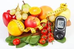 Glucometer för att kontrollera sockernivån, frukter med grönsaker och cm, sockersjuka och sund livsstil Royaltyfria Foton