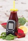 Glucometer för att kontrollera sockernivån och ny rödbetafruktsaft E royaltyfri foto