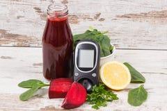 Glucometer f?r att kontrollera sockerniv?n och ny r?dbetafruktsaft E royaltyfria bilder
