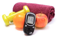 Glucometer, fresh fruits and dumbbells with purple towel Stock Images