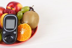 Glucometer and fresh fruits on plate, diabetes and healthy nutrition, copy space for text. Glucose meter for measuring and checking sugar level and fresh fruits Royalty Free Stock Image