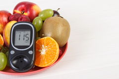 Glucometer and fresh fruits on plate, diabetes and healthy nutrition, copy space for text Royalty Free Stock Photo