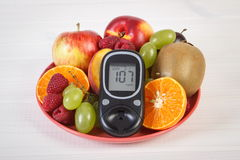 Glucometer and fresh fruits on plate, diabetes and healthy nutrition Stock Photo