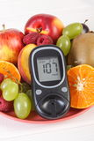Glucometer and fresh fruits on plate, diabetes and healthy nutrition Stock Image