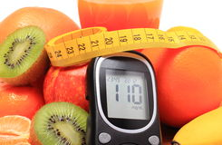 Glucometer, fresh fruits with tape measure and glass of juice Royalty Free Stock Photo