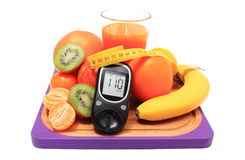 Glucometer, fresh fruits with tape measure and glass of juice Royalty Free Stock Photography