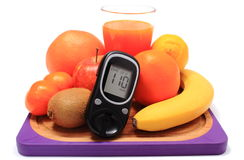 Glucometer, fresh natural fruits and glass of juice Royalty Free Stock Photography