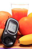 Glucometer, fresh natural fruits and glass of juice Stock Photos