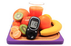 Glucometer, fresh natural fruits and glass of juice Royalty Free Stock Photos