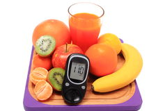 Glucometer, fresh natural fruits and glass of juice Stock Photo